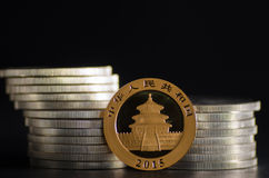 Chinese Gold Panda Coin in front of silver coins.  royalty free stock images