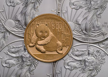 Chinese Gold Panda ontop of US Silver Eagles Stock Photography