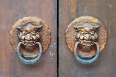 Chinese golden colored door knockers on a wooden gate Royalty Free Stock Images