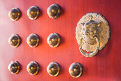 Chinese golden door knocker on a red gate Royalty Free Stock Photography