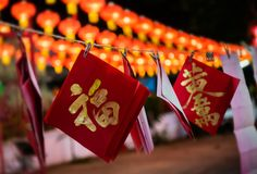 Chinese golden good words written. Chinese golden good word  in the red paper hanging with rope in night low lighting and dark shadow royalty free stock photo