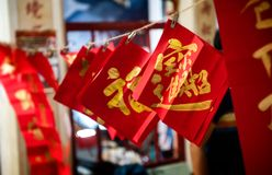 Chinese golden good words written. Chinese golden good word  in the red paper hanging with rope in night low lighting and dark shadow stock photography