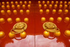 CHINESE GOLDEN LION ON RED DOOR Royalty Free Stock Photos