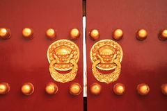 Chinese golden lion on red door. Closed Stock Photos