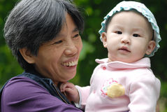 Chinese grandma and baby. In the park Royalty Free Stock Image