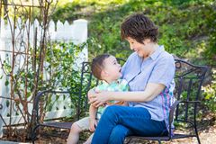 Chinese Grandmother and Mixed Race Child Sit on Bench Outdoors. Chinese Grandmother and Mixed Race Child Talking with One Another on Bench Outdoors royalty free stock photo