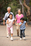 Chinese Grandparents Walking Through Park Royalty Free Stock Image