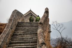 The two men climb the stairs on the Great Wall of China. stock image