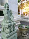 Chinese green granite statue, Thai religion Chinese fetish statue, garden and big jar in background with sun ray. royalty free stock image