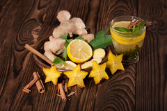 Chinese green tea. A cup of mint tea with lemon and cinnamon. Exotic carambola, ginger and cup of hot tea on a wooden background. A traditional Chinese green Royalty Free Stock Photos