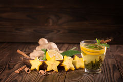 Chinese green tea. A cup of mint tea with lemon and cinnamon. Exotic carambola, ginger and cup of hot tea on a wooden background. Stock Photography