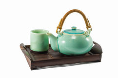 Chinese green teapot and teacups on the wooden trivet Stock Photography