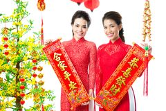 Chinese greetings. Two pretty girls wishing prosperity and happy family life in New Year royalty free stock photo
