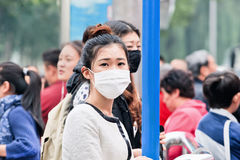 Chinese gril with breath protection against smog, Beijing, China. BEIJING-OCT. 19, 2014. Chinese girl with a face mask. Beijing raised its smog alert to orange Royalty Free Stock Images