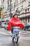 Chinese gril in red rainwear on an e-bike, Shanghai, China. SHANGHAI–MAY 4, 2014. Chinese girl in red rainwear on an e-bike. Shanghai has a humid royalty free stock image