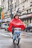 Chinese gril in rode regenkleding op een e-fiets, Shanghai, China royalty-vrije stock afbeelding