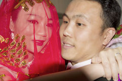 A Chinese groom is holding his bride with arms Stock Photo