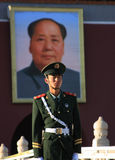 Chinese Guard. A guard standing in front of a big Mao picture in Beijing, China stock photo