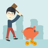 Chinese guy holding a hammer breaking piggy bank. A chinese businessman standing while holding a hammer breaking piggy bank with dollar coins for financial Royalty Free Stock Photos