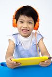 Chinese happy Boy Using Tablet Computer with headphone Stock Images