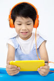 Chinese happy Boy Using Tablet Computer with headphone Stock Photo