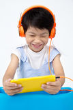 Chinese happy Boy Using Tablet Computer with headphone Royalty Free Stock Photos