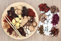 Chinese Herb Selection. Used in herbal medicine with chopsticks on a wooden bowl and calligraphy script on rice paper translated as chinese herbs Stock Photography