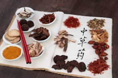 Chinese Herbal Medicine. Chinese herb selection used in herbal medicine with chopsticks on a hemp notebook with calligraphy script on rice paper translated as Stock Photography