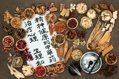 Chinese Acupuncture and Herbal Therapy. Chinese herbal medicine with moxa sticks and acupuncture needles. Calligraphy script reads as traditional ancient chinese Stock Photo