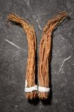 Chinese herbal medicines -- ginseng rootlets. On stone background Stock Images