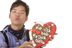Chinese holds Oktoberfest gingerbread heart Royalty Free Stock Photos
