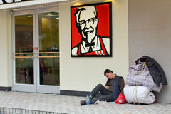 Chinese homeless on sit outside KFC fast food restaurant Stock Images