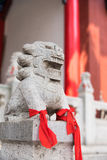 Chinese Imperial Lion, Guardian Lion with a red fabric in their. Legs vertical shot Royalty Free Stock Photos