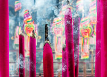 Chinese incenses with smoke. Chinese magenta colored  insences with smoke Royalty Free Stock Photography