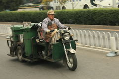 Chinese janitor on a cool green motorcycle Royalty Free Stock Image