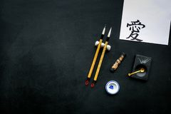 Chinese or japanese calligraphy concept. Hieroglyph love near traditional written accessories on black background top royalty free stock images