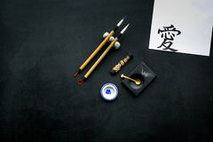 Chinese or japanese calligraphy concept. Hieroglyph love near traditional written accessories on black background top stock photos