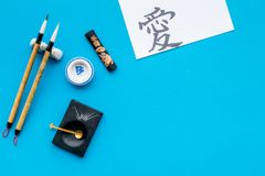 Chinese or japanese calligraphy concept. Hieroglyph love near traditional written accessories on blue background top royalty free stock images
