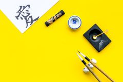 Chinese or japanese calligraphy concept. Hieroglyph love near traditional written accessories on yellow background top stock image