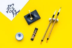 Chinese or japanese calligraphy concept. Hieroglyph love near traditional written accessories on yellow background top royalty free stock photography