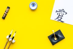 Chinese or japanese calligraphy concept. Hieroglyph love near traditional written accessories on yellow background top royalty free stock photos