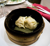 Chinese / Japanese ravioli in a wooden recipient on a white plate close up Royalty Free Stock Images