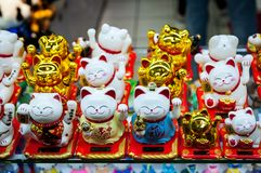 Chinese. Japanese souvenirs. Figurine white and golden cats brings good luck. Golden Maneki Neko cat or Welcome mascot.  stock photo