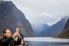 Taking pictures of norwegian fiords. Chinese or japanese tourist taking pictures of beautiful fjords on his mobile during Norway in a nutshell sightseeing tour stock photography