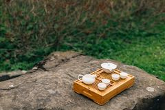 Chinese or japanese white tea set for tea ceremony in green garden. Objects for traditional Chinese or Japanese tea ceremony outdoors stock photos