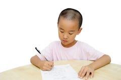 Chinese jongen die bij lijst schrijft Royalty-vrije Stock Fotografie