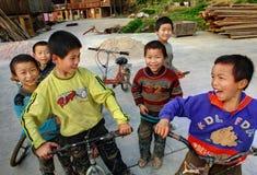 Chinese jongens die fietsen berijden op de volkeren van het etnische dorp. Stock Foto's