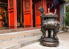 Chinese joss stick pot in front of red door of chinese temple in Stock Photo