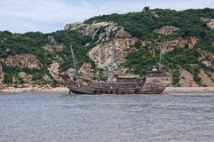 Chinese Junk Boat. A chinese junk boat moving past a small island near Zhoushan on its way to the island of  Putuoshan located in the East Sea in Zhejiang Royalty Free Stock Image