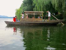 Chinese Junk Boat Paddled Out at Lake. People relaxing on a junk boat paddled out on a Chinese lake Royalty Free Stock Photography